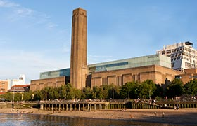 The industrial exterior of the Tate Modern on the banks of the Thames river