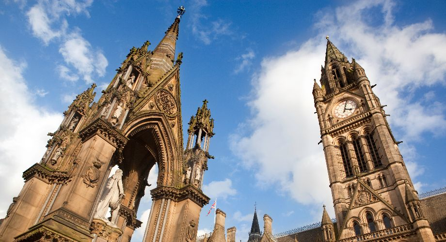 Manchester's neo-Gothic Town Hall against a partly cloudy sky