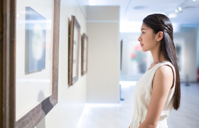 A woman looks at a painting in a gallery