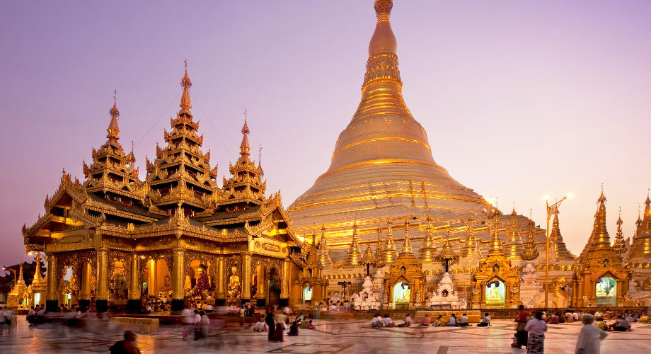 Exterior of the gold Shwedagon Pagoda in Yangon at dusk